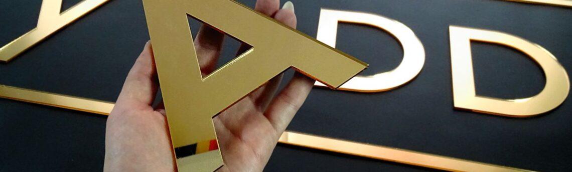 Złote lustrzane logo, litery – reklama salonu