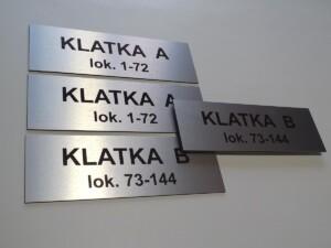 druk na tabliczkach oznakowania mieszkań budynku